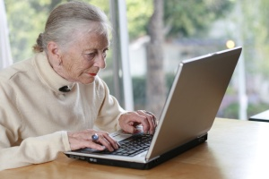 Elderly lady typing on laptop. Shallow DOF.
