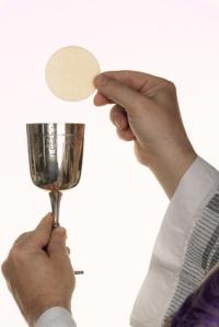 katholischer Priester bei der Kommunion im Gottesdienst